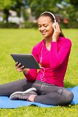 fitness, park, technology and sport concept - smiling african american woman with tablet pc computer