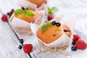 Tasty cupcakes with fruits on table close-up