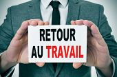 businessman holding a signboard with the text retour au travail, back to work in french, written in