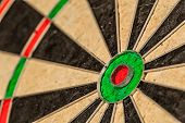 Success hitting target aim goal achievement concept background - bull's eye of darts board close up