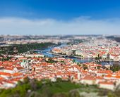 Aerial view of Charles Bridge over Vltava river and Old city from Petrin hill Observation Tower with tilt shift toy effect shallow depth of field. Prague, Czech Republic