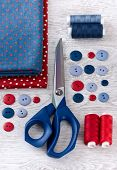 Scissors, Threads, Fabric And Buttons On Wooden Table