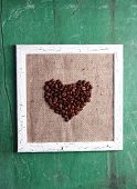 Wooden frame and heart made with coffee grains on wooden background