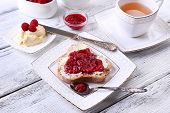 Fresh toast with  homemade butter and raspberry jam on plate on wooden background