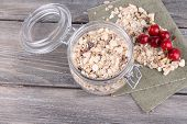 Homemade granola in glass jar, on color wooden background