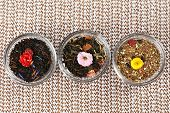 Assortment of dry tea in glass bowls on table