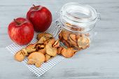 Fresh apples and dried apples in glass jar, on color wooden background