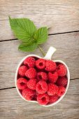 Fresh ripe raspberries bowl on wooden table background