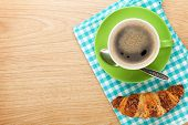 Cup of coffee and fresh croissant on wooden table with copy space