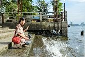 A Cute Asian Girl Kneeling Near The Riverside Dock While Water Splashing In
