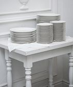 Set of clean plates at the white table  in the restaurant.