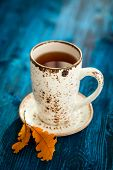 Cup of tea and autumn leaves on blue wooden background.Soft focus