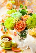 Autumnal table setting with  bunch of autumn flowers and cup of tea