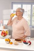 Elderly woman drinking orange juice, preparing healthy breakfast with brown bread and fruits.