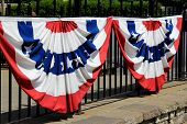 Red,white and blue banners on black fence