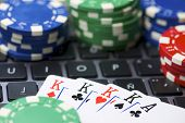 Casino chips and cards stacking on a laptop