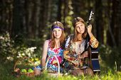 stock photo of hippy  - Two hippie girls with guitar in a summer forest - JPG
