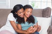 Happy mother and daughter using smartphone together on sofa at home in living room