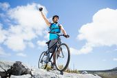 Fit man cycling on rocky terrain and cheering on a sunny day