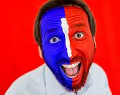 Portrait of adult man with colorful red and blue painted face