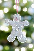 Closeup of gingerbread man hanging against Christmas lights