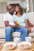 Happy couple relaxing on the couch with juice at home in the living room