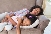Pretty mother sleeping with her daughter on the couch at home in the living room