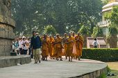 Buddhist Monks, Followed By Pilgrims, Circle The Dhamekh Stupa.