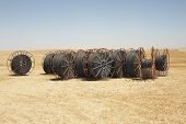 Spools of irrigation hose on arid landscape against clear sky
