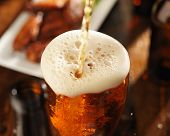 pouring beer into glass with bbq chicken wings in background 01