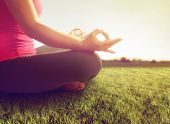 hands of a woman meditating in a yoga pose on the grass toned with a soft sunny filter
