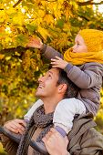 father enjoying colder season outdoor in park teaching leaves