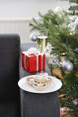 Champagne flute and mince pies on sofa by Christmas tree
