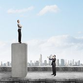 Businesswoman standing on top of bar and businessman screaming in megaphone