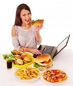 Woman eating fast food at work. Isolated.