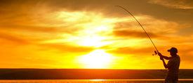 stock photo of jerks  - Mature man fishing on the pond at sunset - JPG