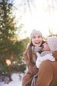 Cheerful couple in winterwear having fun in natural environment