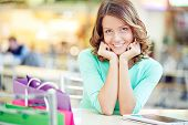 Young charming woman having rest after shopping