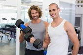 Portrait of sporty young men exercising with dumbbells in the gym