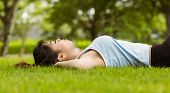 Side view of healthy and beautiful young woman lying on grass in park