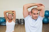 Portrait of young couple stretching hands behind back in yoga class