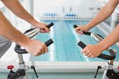 Close up mid section of fit young couple working on exercise bikes at the gym