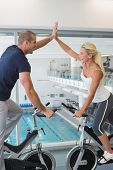Side view of smiling fit couple giving high five while working on exercise bikes at the gym
