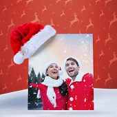 festive young couple against orange reindeer pattern