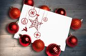 Hanging red christmas decorations against bleached wooden planks background