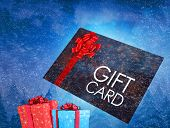 Composite image of flying gift card and presents against snowing sky