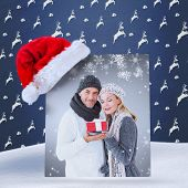 happy winter couple with gift against blue reindeer pattern