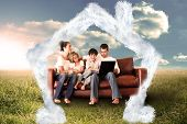 Happy family using the laptop in a field against house outline in clouds