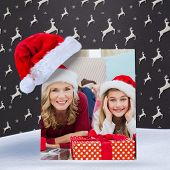 Festive little girl with mother surrounded by gifts against grey reindeer pattern