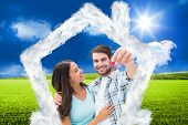 Happy young couple showing new house key against sunny green landscape